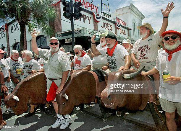 """Ernest Hemingway look-alikes """"run"""" with fake bulls, 22 July 2000, during Key West's annual Hemingway Days Festival that concludes 23 July. The event,..."""