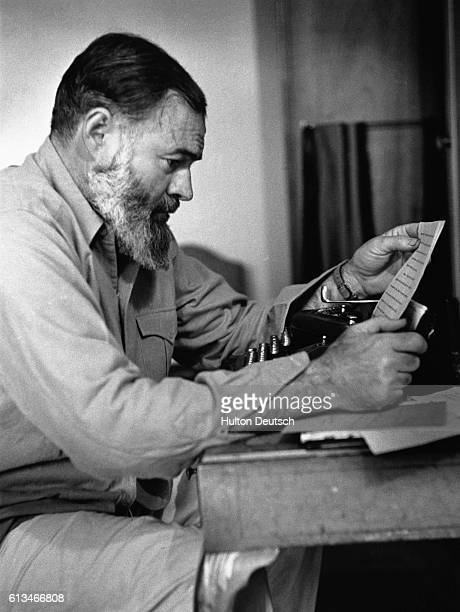 Ernest Hemingway peruses a page of his writing from a typewriter at his desk.