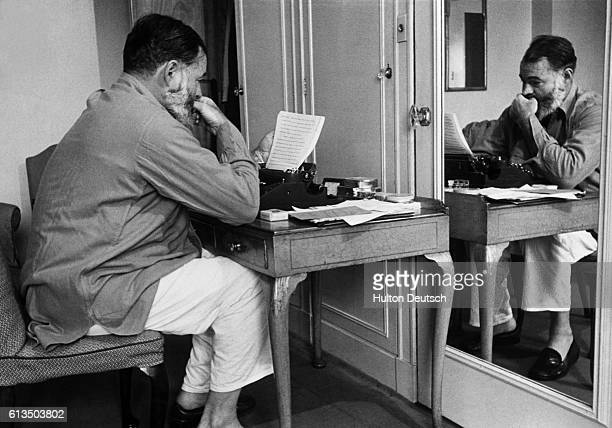 Ernest Hemingway sits at his typewriter and reads his writings during his World War II work as a war correspondent