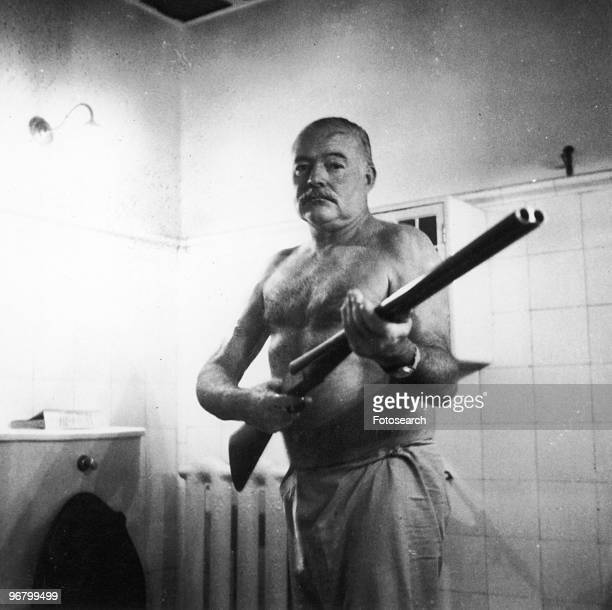 Ernest Hemingway standing with shot-gun indoors circa 1950s. .