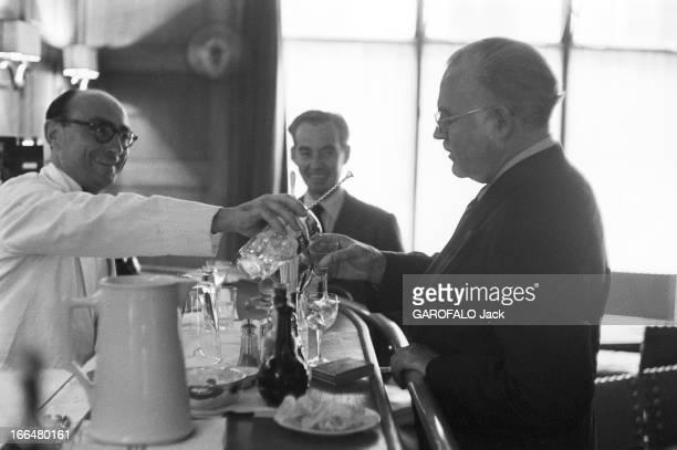 Ernest Hemingway Visiting Paris In France Juillet 1953 Ernest HEMINGWAY aux courses hippiques d' Auteuil Au bar un serveur en veste blanche sert à...