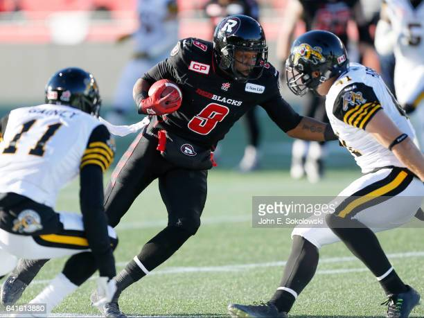 Ernest Jackson of the Ottawa REDBLACKS tries cut between Ed Gainey and Erik Harris of the Hamilton TigerCats during the CFL Eastern Final Playoff...