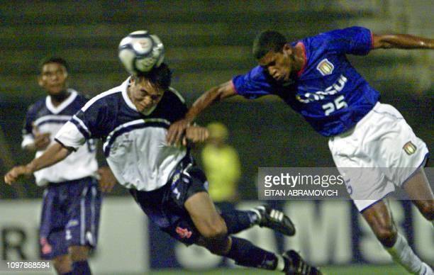 Ernesto Arakaki of Peru 's Alianza Lima hits the ball with his head as Marcos Senna del Sao Caetano of Brazil jumps for the ball 28 March 2002 in...