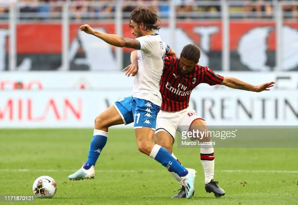 Ernesto Torregrossa of Brescia Calcio competes for the ball with Ricardo Rodriguez of AC Milan during the Serie A match between AC Milan and Brescia...
