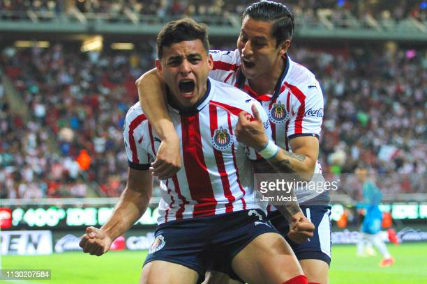 Ernesto Vega of Chivas celebrates with teammate after scoring the first goal of his team during the seventh round match between Chivas and Atlas as...