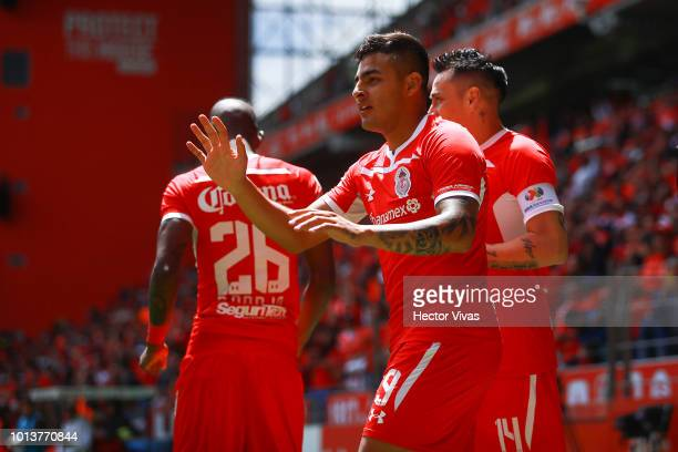 Ernesto Vega of Toluca celebrates with teammates after scoring the first goal of his team during the third round match between Toluca and Chivas as...