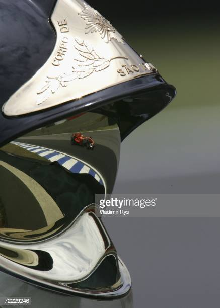 Ernesto Viso of Venezuela and Spyker MF1 is seen reflected in the helmet of a fireman during the first practice for the Brazilian Formula One Grand...
