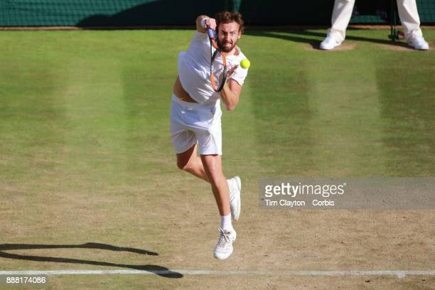 Ernests Glubis of Latvia in action against Novak Djokovic of Serbia on Centre Court in the Gentlemen's Singles Competition during the Wimbledon Lawn...