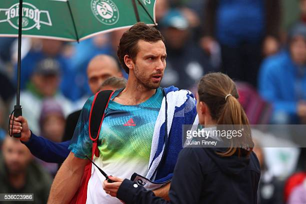 Ernests Gulbis of Latvia attempts to walk off court because of the falling rain but is stopped by the Umpire during the Men's Singles fourth round...