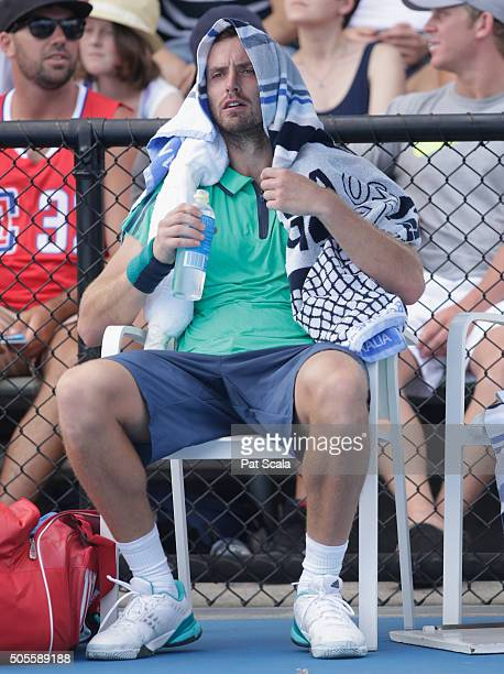 Ernests Gulbis of Latvia has a drink in between games in his first round match against Jeremy Chardy of France during day two of the 2016 Australian...
