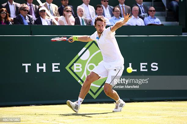 Ernests Gulbis of Latvia hits a forehand against Milos Raonic of Canada during The Boodles Tennis Event at Stoke Park on June 17 2014 in Stoke Poges...