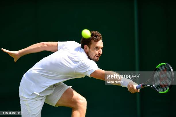 Ernests Gulbis of Latvia plays a backhand in his Men's Singles first round match against Leonardo Mayer of Argentina during Day one of The...