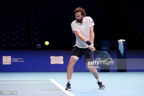 Ernests Gulbis of Latvia plays a backhand in his Men's Singles first round match against Roberto Marcora of Italy on day three of the Singapore...