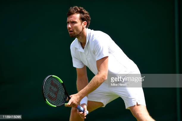 Ernests Gulbis of Latvia prepares to return serve in his Men's Singles first round match against Leonardo Mayer of Argentina during Day one of The...