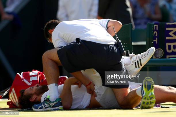 Ernests Gulbis of Latvia receives treatment from the medical team during the Gentlemen's Singles third round match against Novak Djokovic of Serbia...