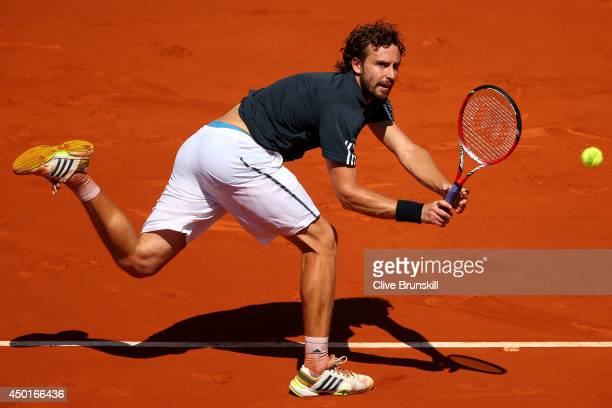 Ernests Gulbis of Latvia returns a shot during his men's singles semifinal match against Novak Djokovic of Serbia on day thirteen of the French Open...