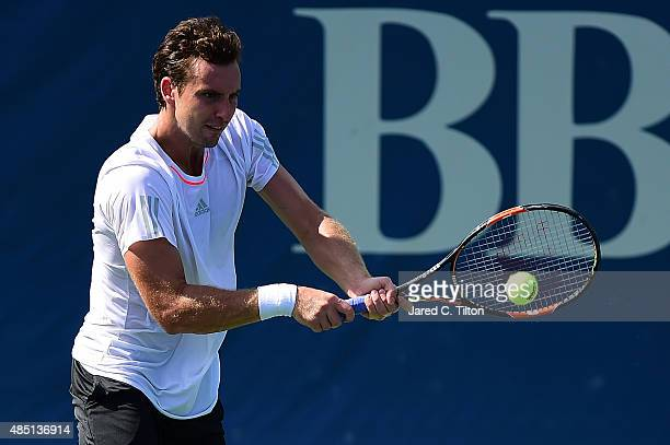Ernests Gulbis of Latvia returns a shot from Lukas Rosol of Czech Republic during the first day of the WinstonSalem Open at Wake Forest University on...