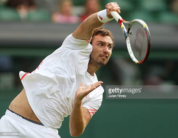 Ernests Gulbis of Latvia serves the ball during his gentlemen's singles first round match against Tomas Berdych of Czech Republic on day one of the...