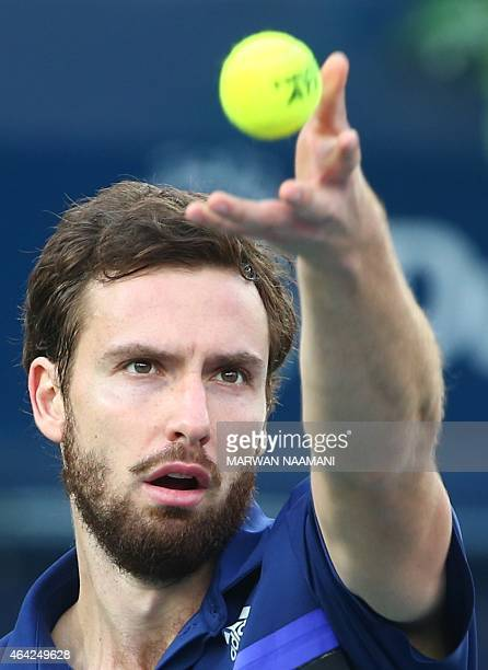 Ernests Gulbis of Latvia serves the ball to Denis Istomin of Uzbekistan during their match in the first day of the ATP Dubai Duty Free Tennis...