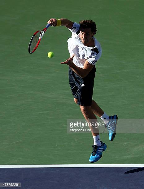 Ernests Gulbis of Latvia serves to John Isner during the BNP Paribas Open at Indian Wells Tennis Garden on March 14 2014 in Indian Wells California