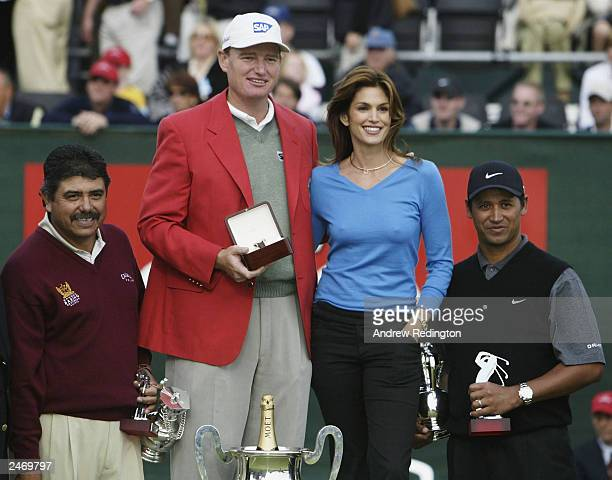 Ernie Els of South Africa celebrates his victory with Cindy Crawford as Eduardo Romero and Michael Campbell look on at the Omega European Masters on...