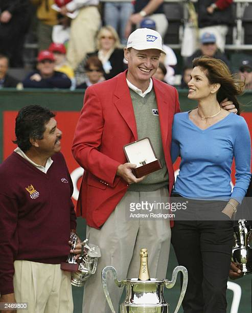 Ernie Els of South Africa celebrates his victory with Cindy Crawford as Eduardo Romero looks on at the Omega European Masters on September 7 2003 at...