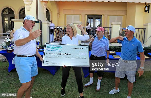 Ernie Els of South Africa holds the cheque with his wife Liezl Els showing the extra one million dollars to the money raised at the proam organised...