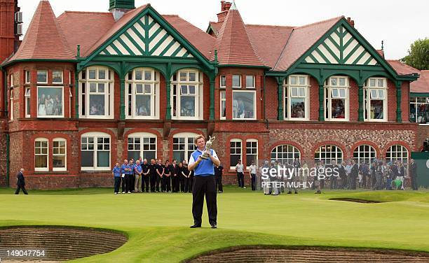 Ernie Els of South Africa holds the Claret Jug 'The Golf Champion Trophy' in front of the clubhouse on the 18th green after winning the 2012 British...