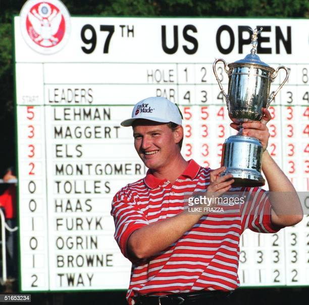 Ernie Els of South Africa holds the US Open trophy with the leader board in the background 15 June after winning the 1997 US Open Championship at...