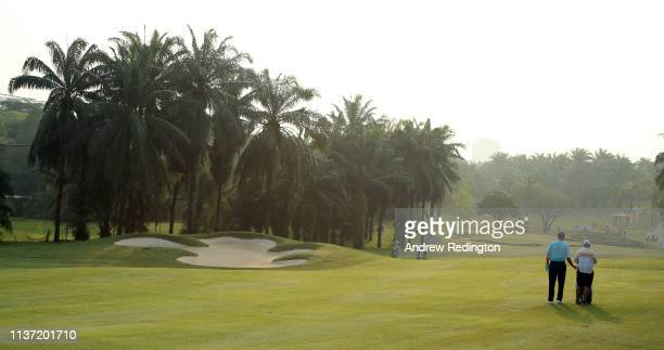 Ernie Els of South Africa is pictured with his caddie Ricci Roberts on the tenth hole on Day One of the Maybank Championship at Saujana Golf Country...