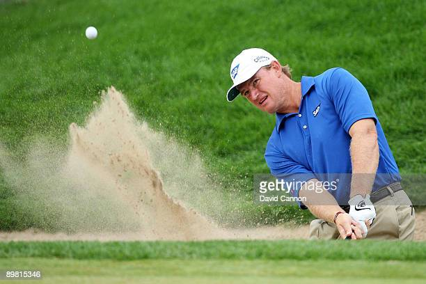 Ernie Els of South Africa plays a bunker shot on the 18th hole during the third round of the 91st PGA Championship at Hazeltine National Golf Club on...