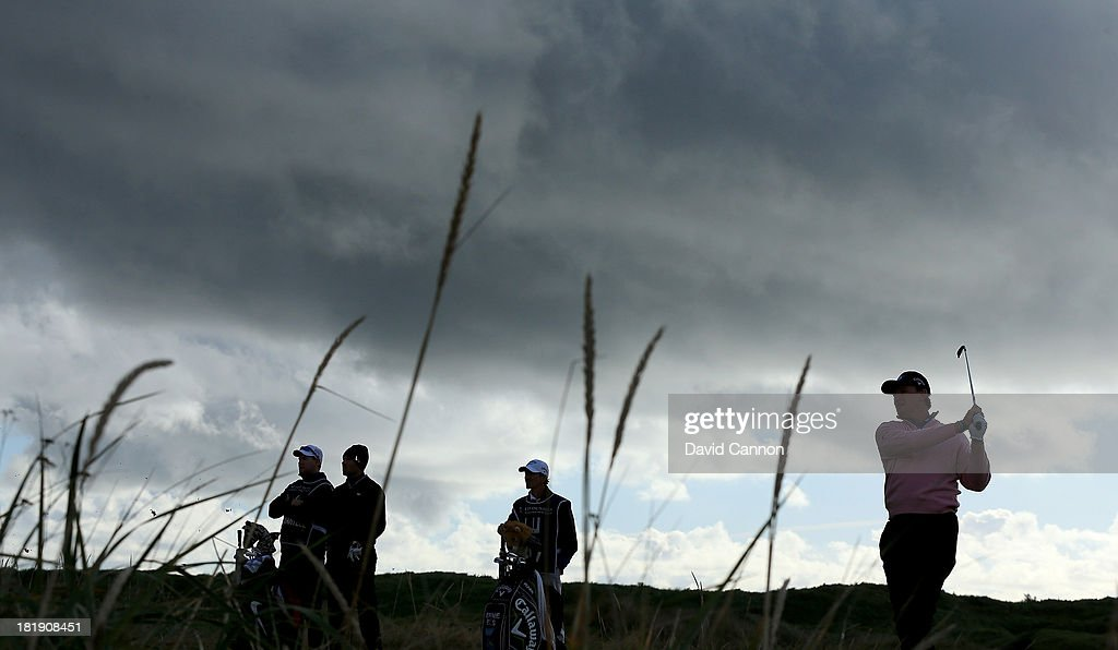 Ernie Els of South Africa plays his tee shot at the par 4, third hole watched by his partner Charl Schwartzel of South Africa and their caddies during the first round of the 2013 Alfred Dunhill Links Championship on the Championship Course at Carnoustie on September 26, 2013 in Carnoustie, Scotland.