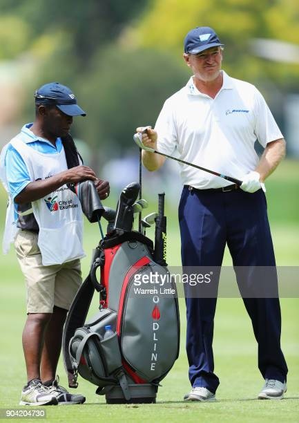 Ernie Els of South Africa takes a club from his bag with his caddie on the 7th hole during day two of the BMW South African Open Championship at...