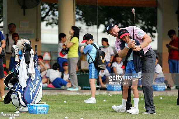 Ernie Els of South Africa teaches a young girl during the golf clinic held at the Tuen Mun Golf Centre prior to the start of the 2014 Hong Kong open...