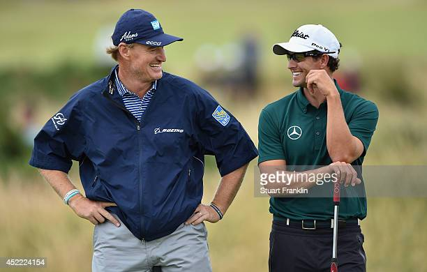 Ernie Els of South Africa waits with Adam Scott of Australia during a practice round prior to the start of The 143rd Open Championship at Royal...