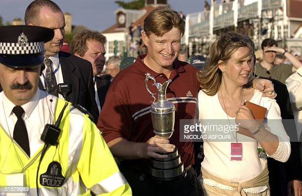 Ernie Els of South Africa walks off the 18th hole holding the Claret Jug with his wife Leizel Els after winning The 131st Open Championship at...