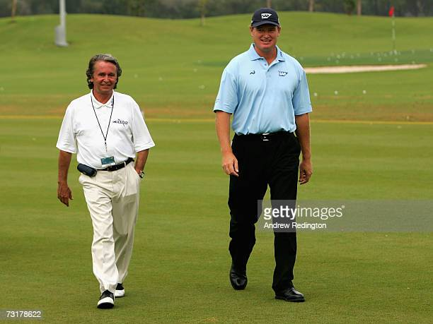 Ernie Els of South Africa walks with his mental coach Jos Vantisphout before the second round of the Dubai Desert Classic on the Majilis Course at...