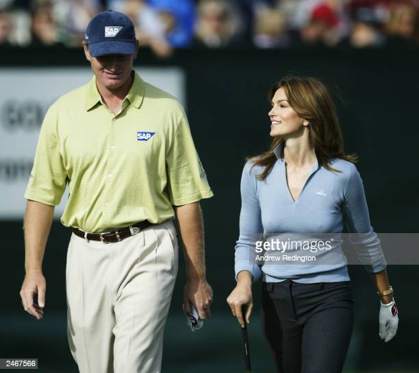 Ernie Els walks with model Cindy Crawford during a promotional event following the third round of the Omega European Masters on September 6 2003 at...