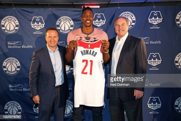 Ernie Grunfeld and Scott Brooks pose for a photo with Dwight Howard of the Washington Wizards during a press conference at the Capital One Arena on...