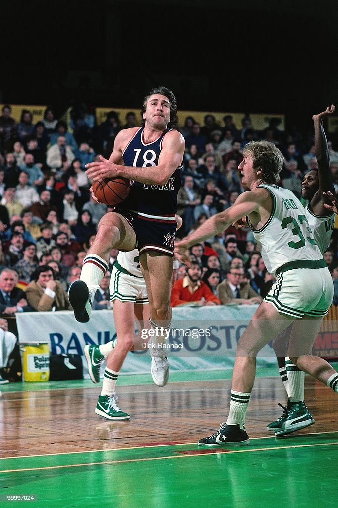 Ernie Grunfeld #18 of the New York Knicks drives to the basket against Larry Bird #33 of the Bosotn Celtics during a game played in 1983 at the Boston Garden in Boston, Massachusetts.