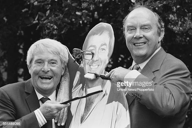 Ernie Wise and Eric Morecambe of British comedy duo Morecambe and Wise pictured together with giant toothbrushes and a cardboard cut out of Des...