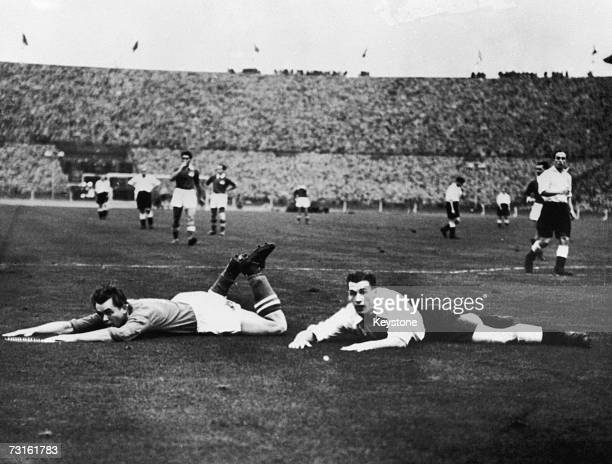 Ernst Happel and Nat Lofthouse sprawled on the pitch near the Austrian goal during an international match between England and Austria at Wembley...