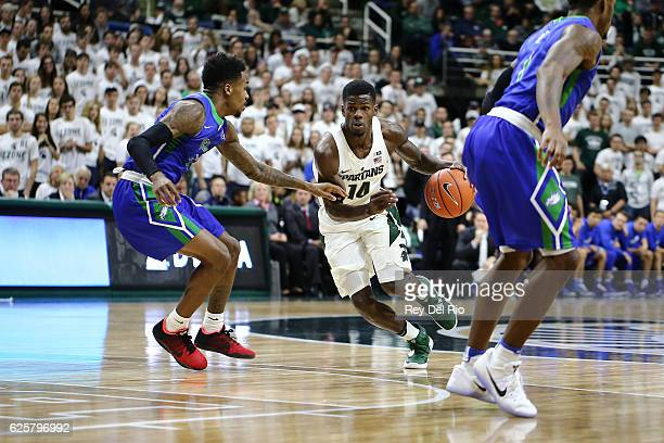 Eron Harris of the Michigan State Spartans handles the ball in the second half against Reggie Reid of the Florida Gulf Coast Eagles on November 20...
