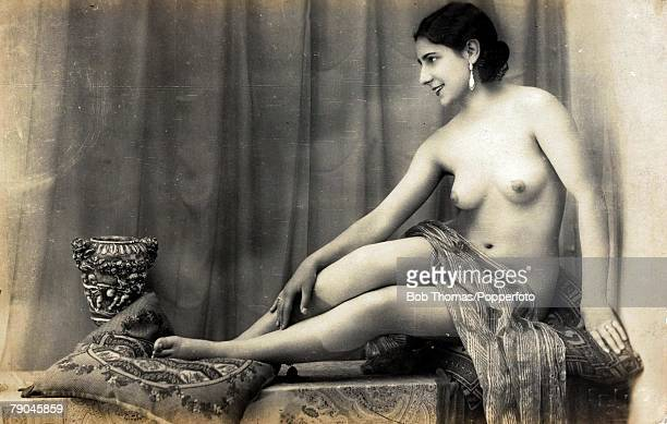 Erotic Postcard circa 1915 Dishabille Dark haired woman her breasts exposed to the camera covered only by a fabric wrap