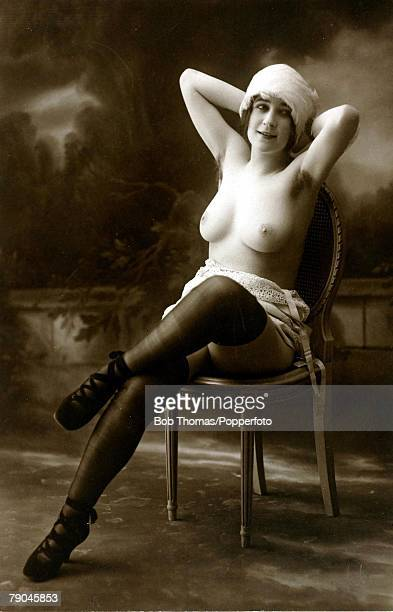 Erotic Postcard circa 1915 Dishabille Dark haired woman sitting on a chair in a studio setting her breasts exposed to the camera