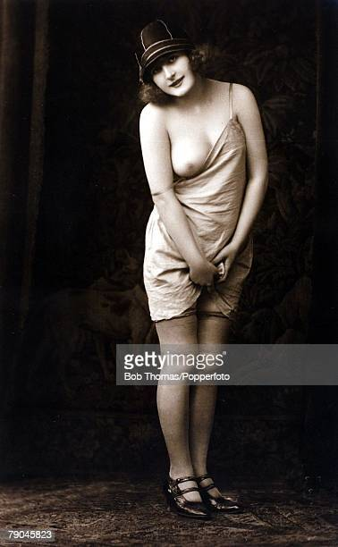 Erotic Postcard circa 1915 Dishabille Dark haired woman wearing a slip pulled down to expose her breast