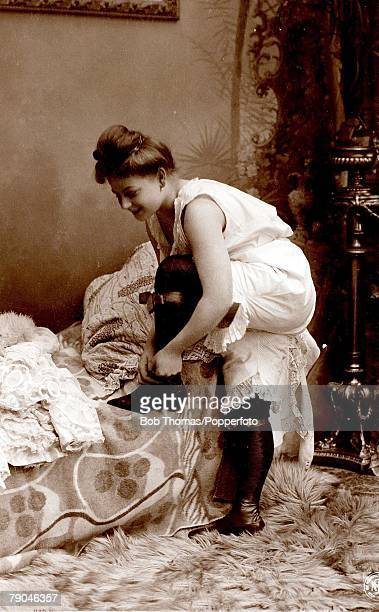 Erotic Postcard circa 1915 Dishabille Woman wearing undergarment one foot on bed lacing her boots