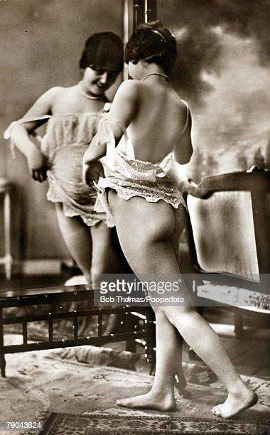 Erotic Postcard circa 1915 Dishabille Young woman exposing her bottom in an image reflected in a mirror