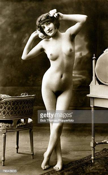 Erotic Postcard circa 1915 Nude Naked young woman full frontal holding a rose whilst standing by a dressing table and chair