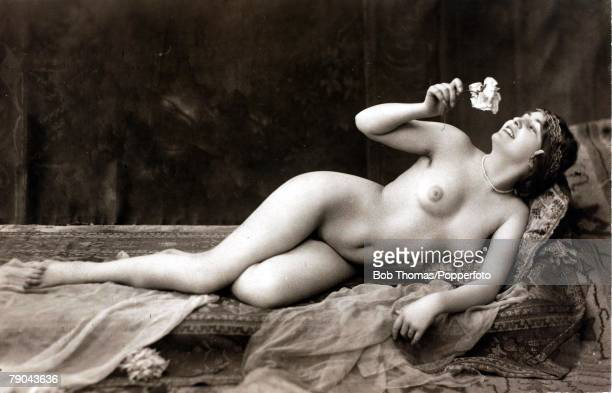 Erotic Postcard circa 1915 Nude Naked young woman full frontal holding a rose reclining against a cushion